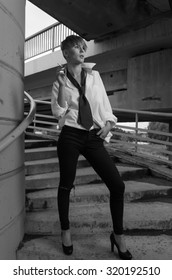 Young woman model in manly staying sitting on stairs. Black white.