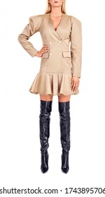 Young woman model wearing jacket dress and knee high boots, posing in studio.Isolated clothes on a white background