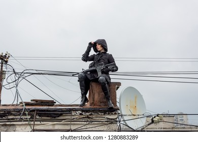 Young woman in modern black techwear style with rifle posing on the rooftop, portrait of redhead woman cyperpunk or   post apocalyptic concept