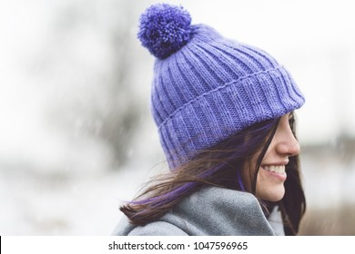 Young woman in modern knitted purple hat outdoors on snowy winter day. Closeup, natural light, no retouch.