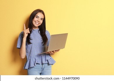 Young woman with modern laptop on color background
