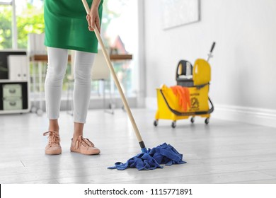 Young woman with mop cleaning floor in office
