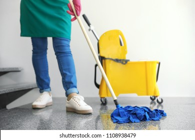 Young woman with mop cleaning stairs