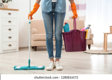 Young woman with mop and detergents in living room, closeup. Cleaning service