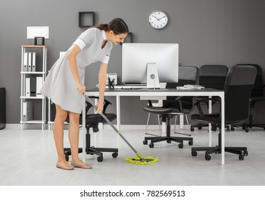 Young woman mopping floor in office