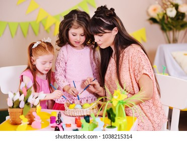 young woman mother with little girls daughters preparing for the celebration of Easter and coloring eggs sitting at the table on the background of the Easter decor.