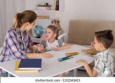 A young woman - a mother, a nanny or a teacher,  draws with  children - a boy and a girl. They sit at the table and draw with pencils.  The girl emotionally asks a question to a woman.