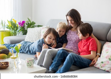 Young woman, mother with three kids, reading a book at home, hugging and laughing, family happiness