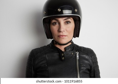 Young woman in motorcycle concept. Extreme girl in bike helmet and motor protection race suit on white background