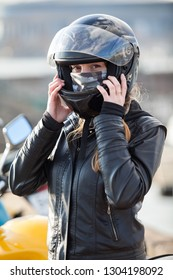 Young woman motorcyclist put on crash helmet for riding bike on urban roads