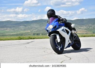 Young woman motorcyclist speeding on tarmac racetrack - former airport runway near the town of Dupnitsa, Bulgaria