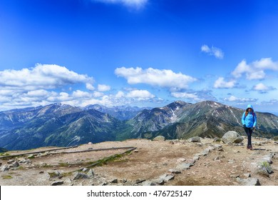 young woman in mountains, background of sky and clouds