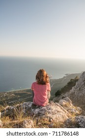 Young woman in the mountains of Crimea, south of Russia, background - Black Sea and sky
