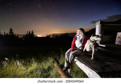 Young woman in the mountains watching beautiful starry night from a wooden hut porch together with her dog. City lights are on the horizon. Copy space. Concept of mountain retreat