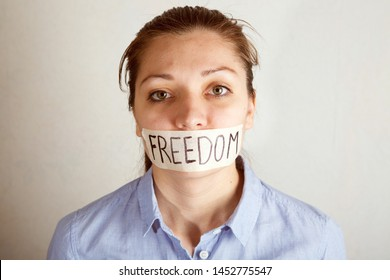 Young woman with mouth covered with tape. Concept of forbidden opinion.