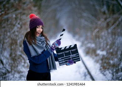 Young woman with movie clapper on railways