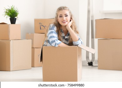 Young woman in moving box at new home