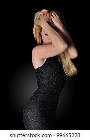 A young woman is moving and has curve shape on a black background. She is hiding her face and has blond hair.