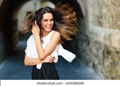 Young woman moving her long hair in urban background. Female in casual clothes with care hairstyle in Granada, Andalusia, Spain.