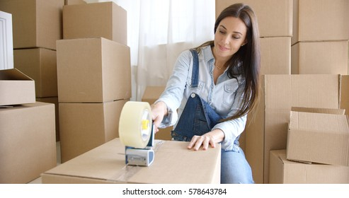 Young woman moving home packing boxes