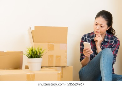 young woman is moving house, sitting among cardboard boxes using a smartphone to research new furniture. mixed race asian chinese model.