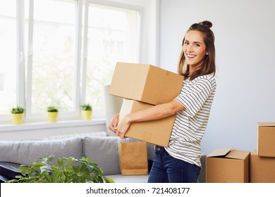 Young woman moving into new apartment holding cardboard boxes with belongings