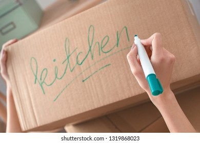 Young woman moving to new place standing writing kitchen word on box with marker pen close-up