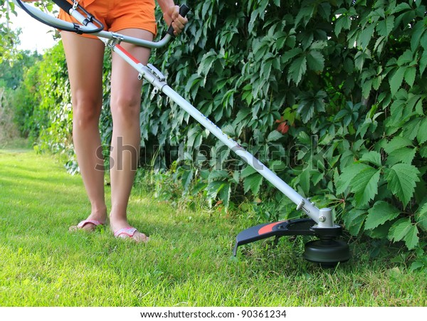 Young woman Mowing the Grass