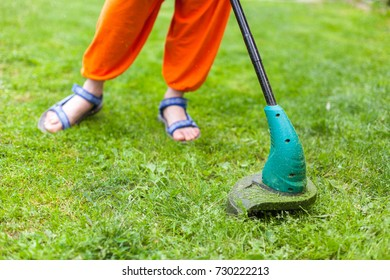 Young woman mowing the grass with a trimmer.