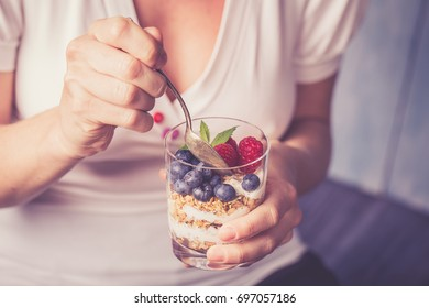 Young woman with muesli bowl. Girl eating breakfast cereals with fresh friuts, nuts, oats and homemade yogurt in glass.