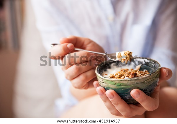 Young woman with muesli bowl. Girl eating breakfast cereals with nuts, pumpkin seeds, oats and yogurt in bowl. Girl holding homemade granola. Healthy snack or breakfast in the morning..