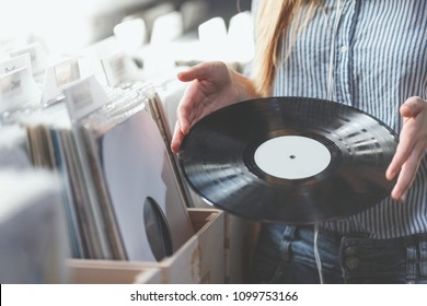 Young woman with music records in a store