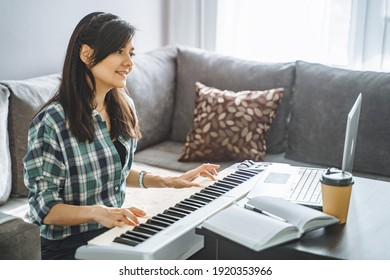 Young woman music teacher playing electric piano teaching remotely using laptop while working from home. Online education and leisure concept.