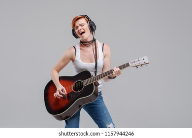 Young woman musician with an acoustic   guitar in hand and in headphones on a gray background. He laughs and plays rock and roll loudly.