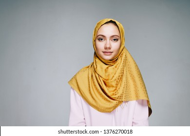 A young woman in a Muslim headscarf and clothes calmly looking into the camera on a white background. Studio