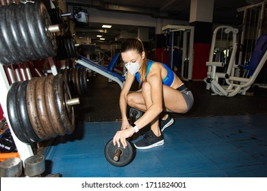 Junge Frau mit n95 Gesichtsmaske, die Gewichte in der Bar während Fitnessstudio Fitness-Training unter Coronavirus Covid-19 Krise.