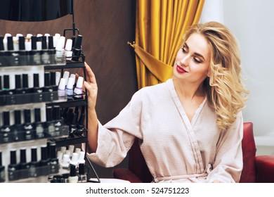 Young woman in nail salon choosing nail polish color to apply