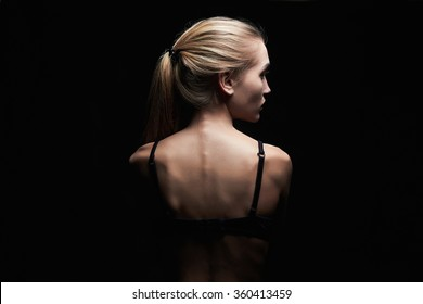 young woman with naked back over black background.sport body girl