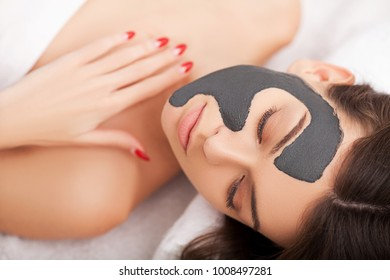 Young woman with natural facial mask in beauty spa
