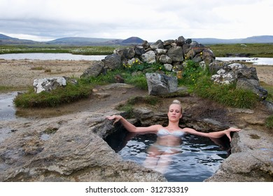 Young woman in natural hot spring in Iceland