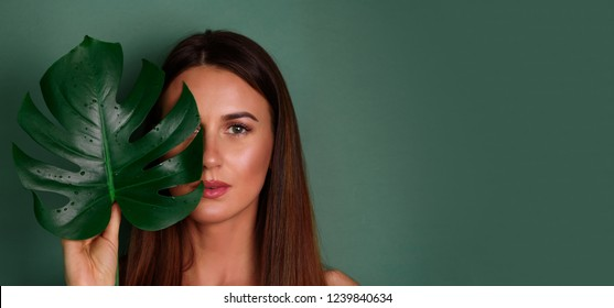 Young woman with natural make up and tropical monstera leaf in hand over green background with copy space. Skin care, pure beauty, body treatment, cosmetics concept. Banner.
