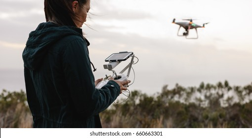 Young woman navigating a flying drone with remote control. Woman in countryside flying drone and taking pictures.