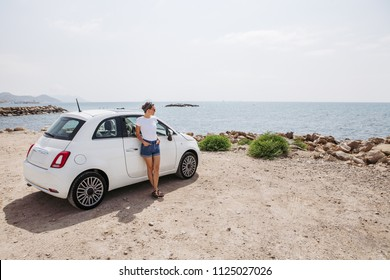 Young woman near car outdoors on sunny day near the sea