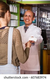 Young woman near counter in chemist's shop