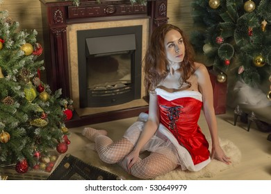 Young woman near fireplace in Christmas
