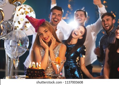 Young woman near her birthday cake at party in club