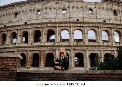 Young woman near italian Colloseum in Rome. All roads will go to Rome