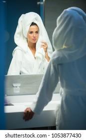 Young woman near a mirror in a hotel in bathrobe.