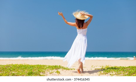 Young woman near the ocean. Back view
