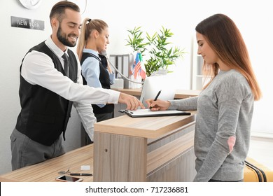 Young woman near reception desk in hotel